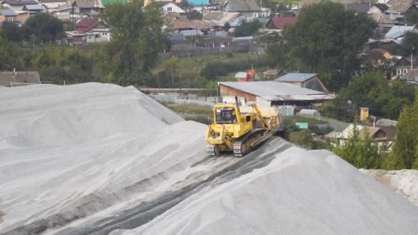 Big yellow excavator working in gravel quarry. Stock footage. Professional Mining industry concept, large construction excavator of yellow color at the construction site located near the city.
