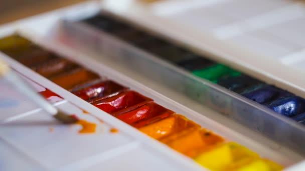 Close-up Künstler mischt Aquarelle mit Pinsel auf Palette. Konzept. Helle Aquarellfarben werden mit Pinsel auf weißer Palette gemischt. Farben und Kreativität