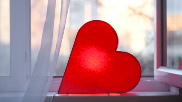 Světlá lampa ve tvaru srdce je na okně. Koncept. Červená lampa ve tvaru srdce stojí u okna a září, aby všem propůjčila lásku. Jasná romantická výzdoba