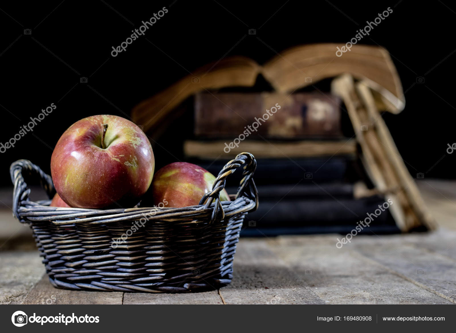 Leckere Äpfel im Korb am Küchentisch. Alte Bücher liegen neben einer ...