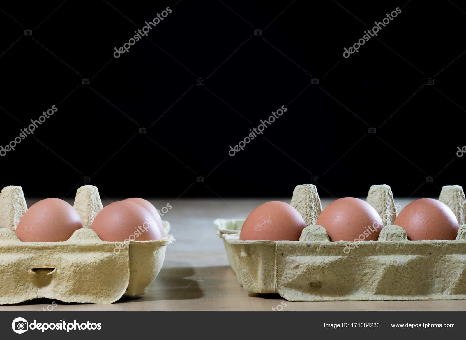 Uova in stampi su un tavolo da cucina in legno. Uovo di gallina in ...