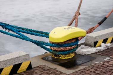 A mooring bollard entwined with a mooring rope. Moored ships at