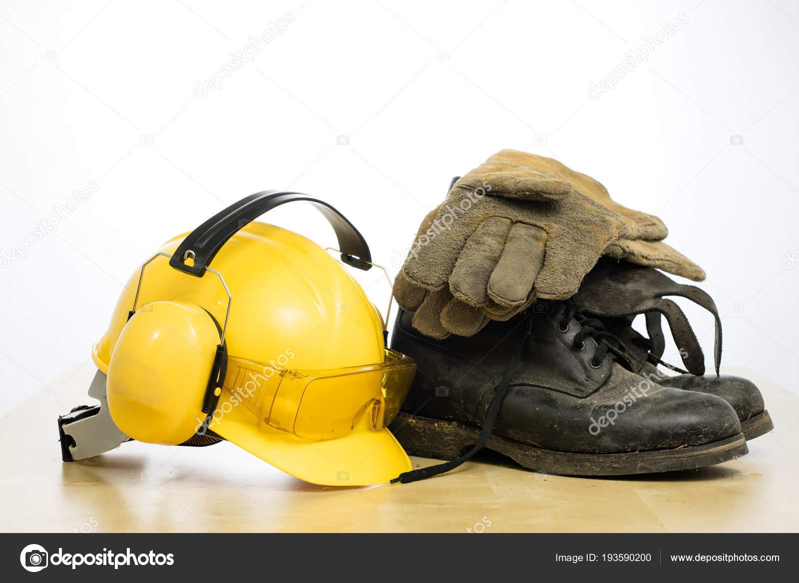 Ochranné přilby a pracovní obuv na dřevěný stůl. Bezpečnost a h– stock  obrázky 55e3029cc30