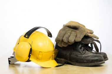 Protective helmet and work boots on a wooden table. Safety and health protection accessories for construction workers. White isolated background. stock vector