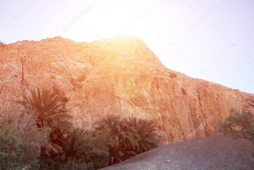 Bright sun at the zenith behind the silhouette of a mountain in
