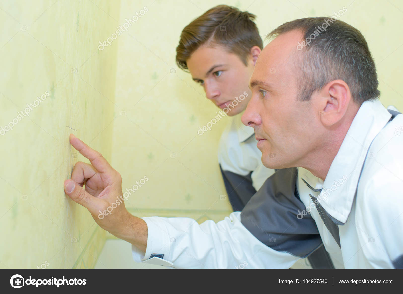 Decorators inspecting wall and decorator — Stock Photo ...