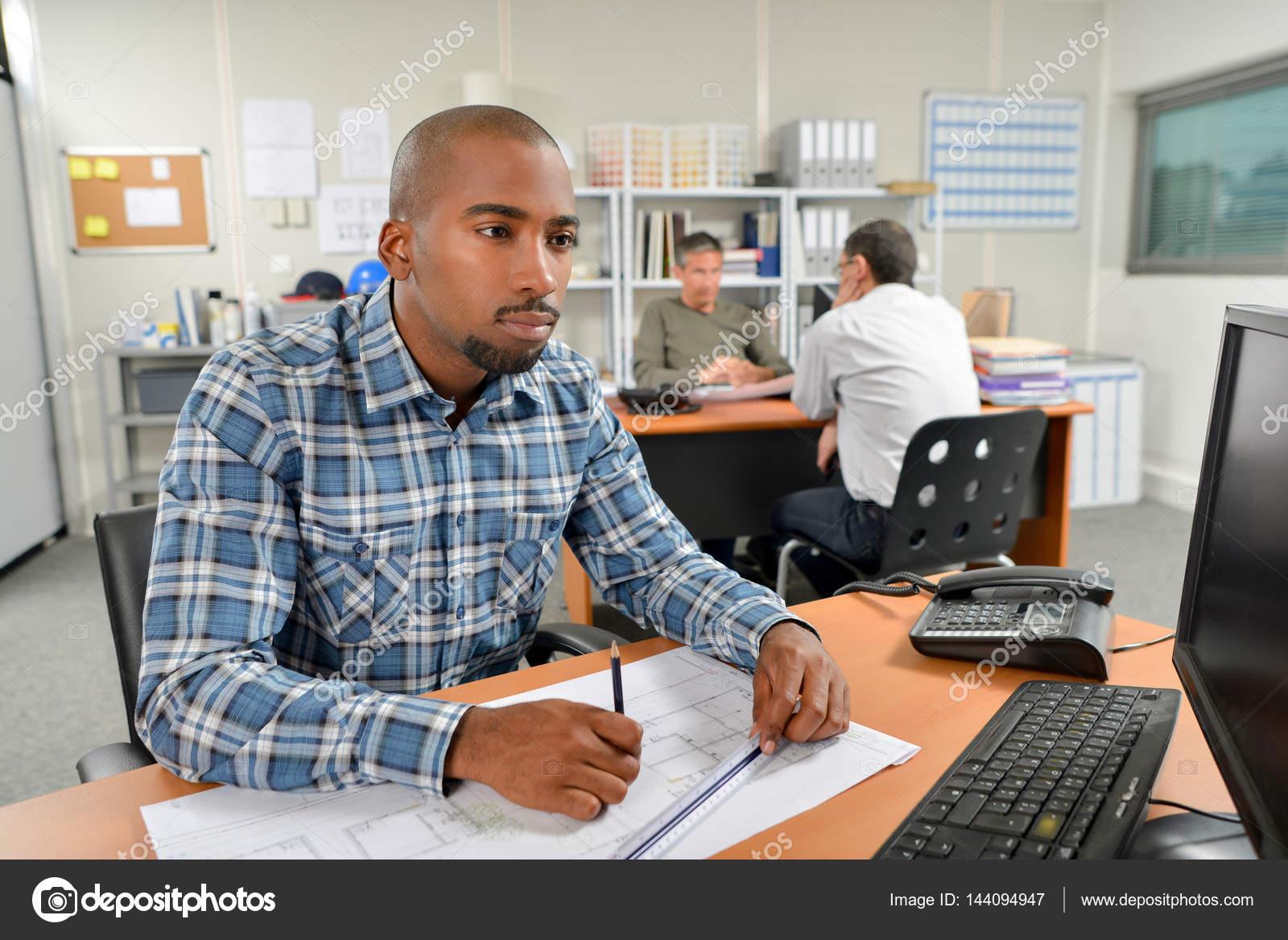 Disegno Uomo Alla Scrivania : Uomo alla scrivania lavorando su disegni in scala u foto stock