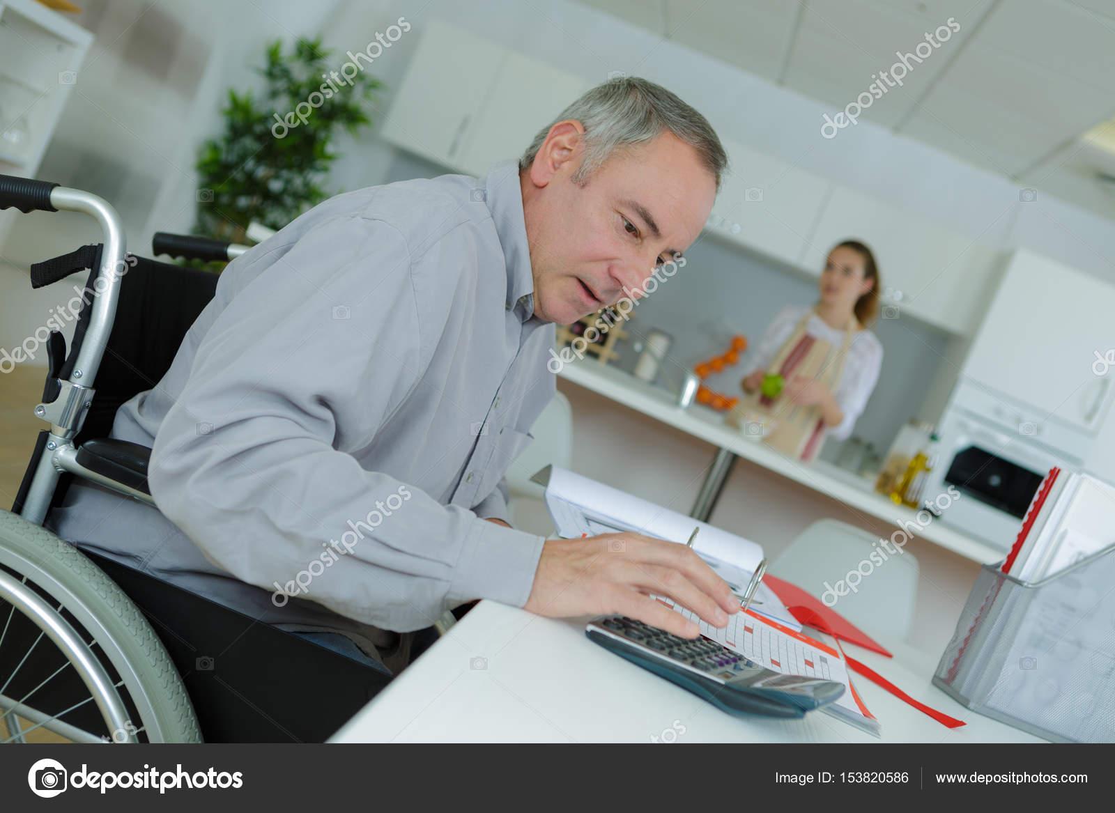 Mann im Rollstuhl erledigen von Büroarbeiten zu Hause — Stockfoto ...