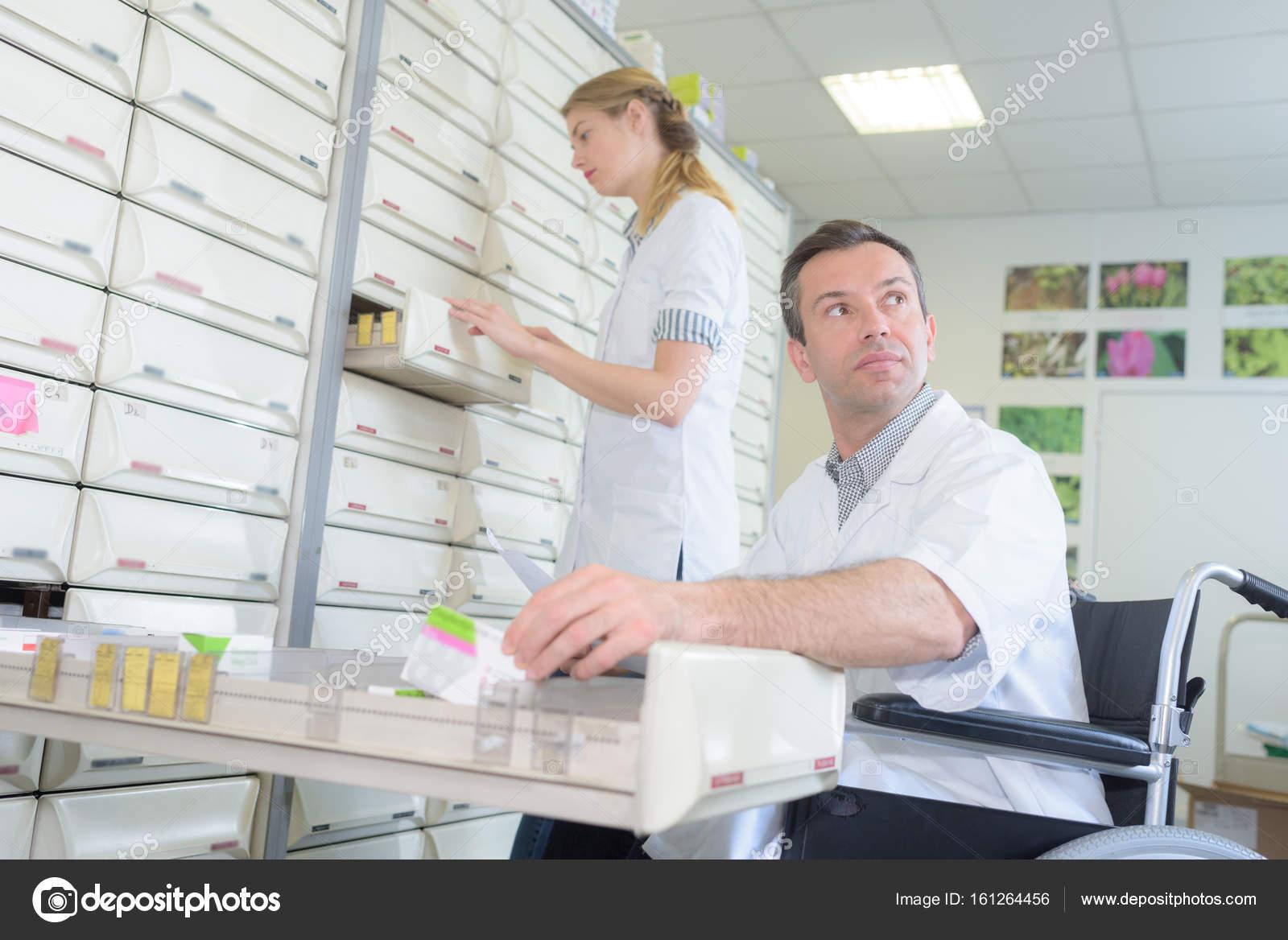 Apotheker stehen und Apotheke Techniker im Rollstuhl — Stockfoto ...