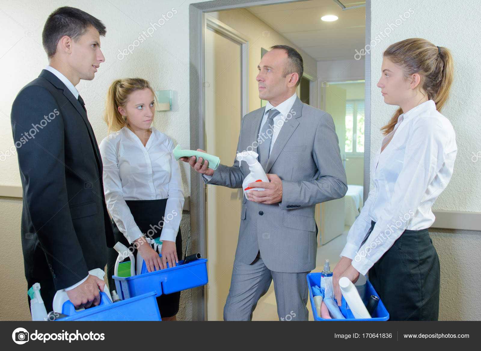 supervisor with hotel personnel looking at cleaning products stock