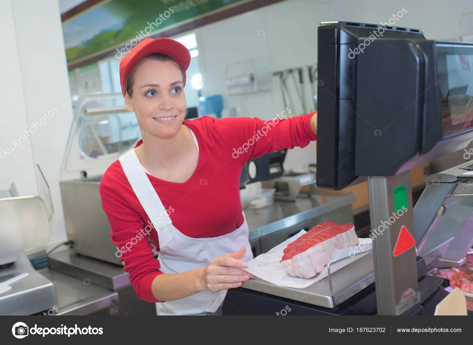 Female Butcher At Display Counter In Butchery Stock Photo