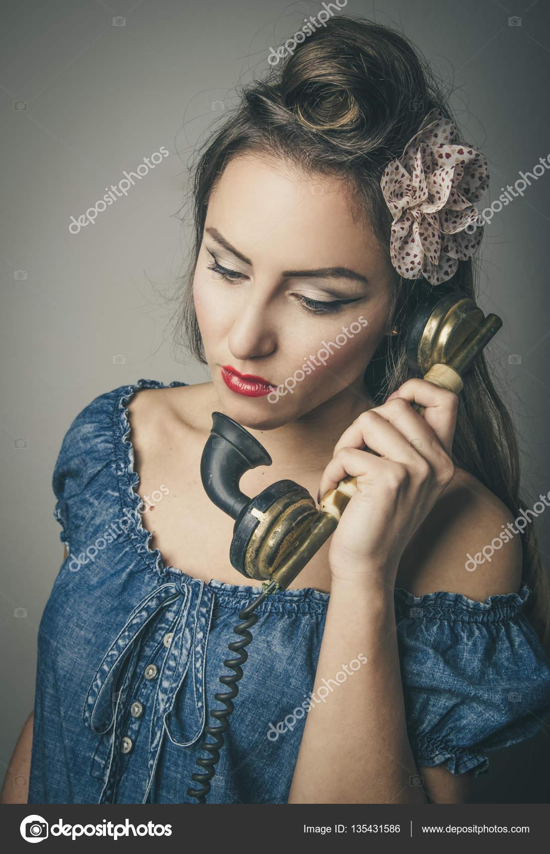 Гламурная привлекательная женщина, держа ее мобильный телефон.