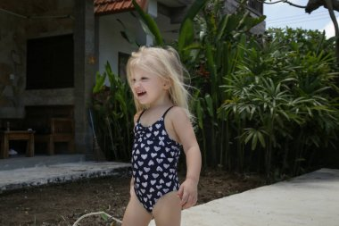Adorable blonde toddler girl enjoying day at the pool. Summer vacation concept.