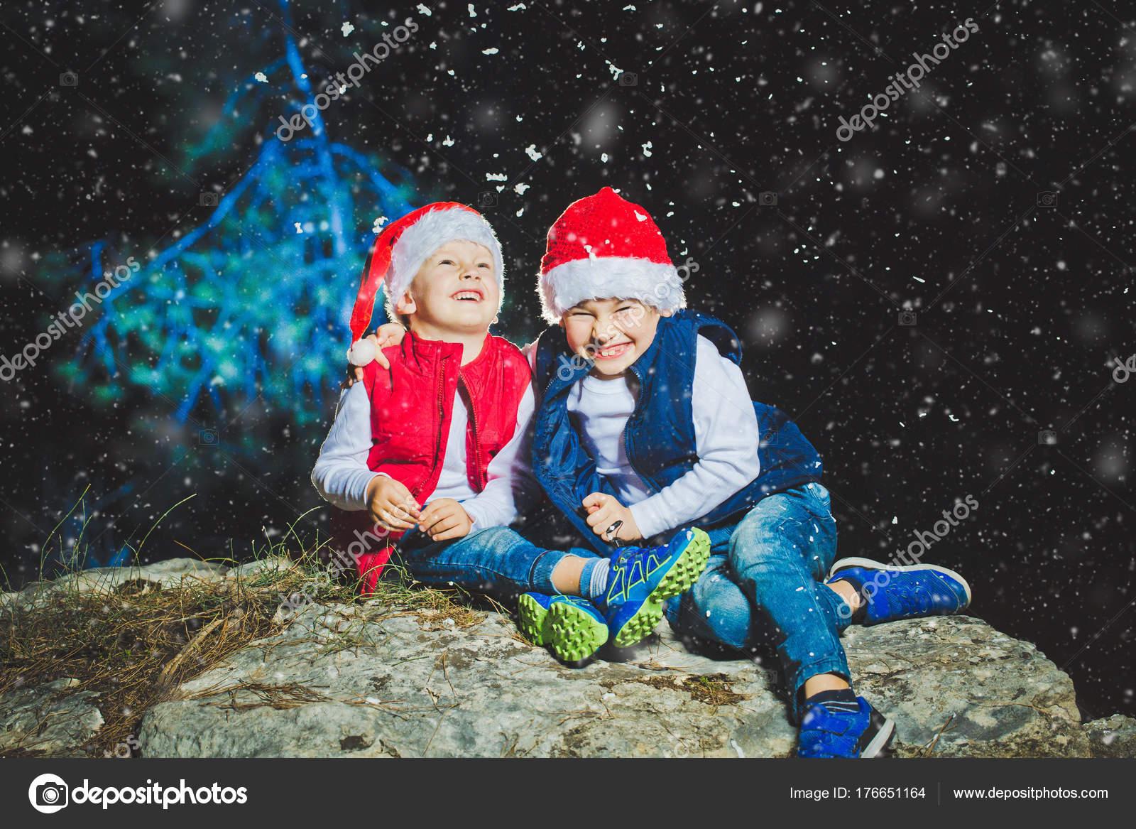 Retrato de chicos lindos gorros de Santa mirando a cámara en noche de  Navidad en el 20543232b4f