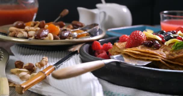 Breakfast of pancakes with berries and dry fruits, defocused background