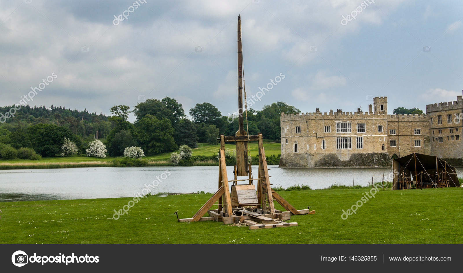 A Medieval Trebuchet With A Moated Castle In The Background Stock