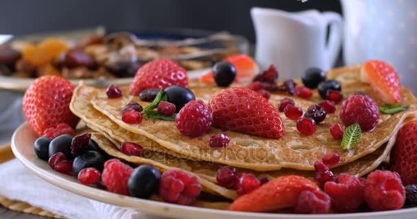 Přidání šlehačka přes palačinky s ovocem a suché plody, pohled shora dolů