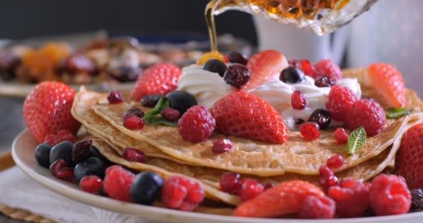 Nalitím javorový sirup na snídani palačinky s ovocem, suché plody a šlehačkou