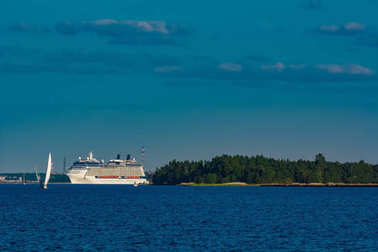 Giant white passenger ship moving past the port on a clear day