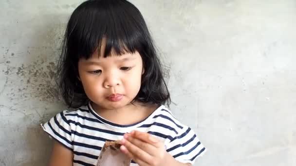 Asijská holčička mají velké oči, stál přední zdi cementu a trochu asijské dívky jí radost jíst čokoládové zmrzliny