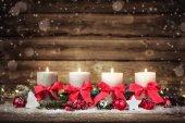 adventliche Dekoration mit vier brennenden Kerzen.