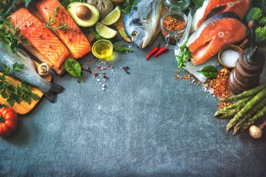 Assortment of fresh fish with aromatic herbs, spices and vegetab