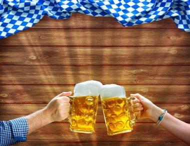 Hands holding up beer mugs under Bavarian flag