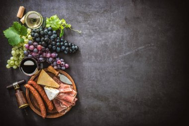 Wineglasses with grapes, cheese, ham and corks