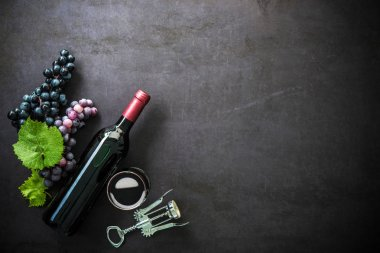 Bottle of red wine, wineglass and grapes