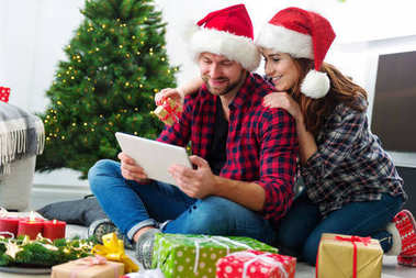 Young couple with Santa Claus hats shopping online Christmas gif