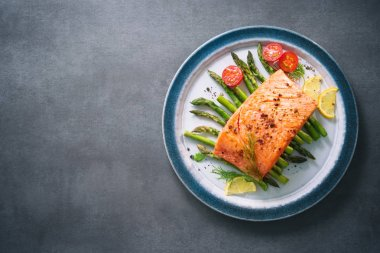 Grilled salmon garnished with green asparagus and tomatoes
