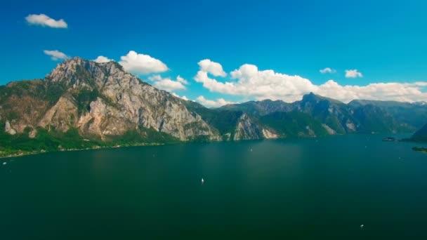 Letecký panoramatický pohled jezero s jachty poblíž venkovské oblasti. Panoramatický pohled s mraky a modrá obloha