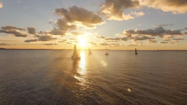 Luftaufnahme von Yachten mit Segel im Meer mit einer schönen malerischen Blick auf den Sonnenuntergang. Yachten im offenen Meer