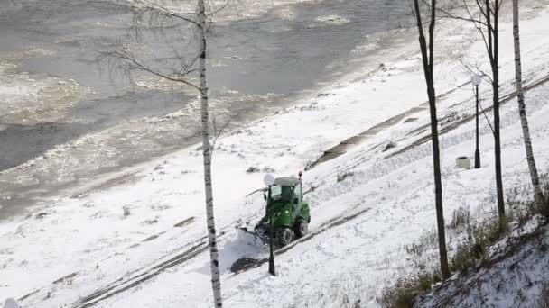 the embankment of the river Vyatka tractor cleans snow