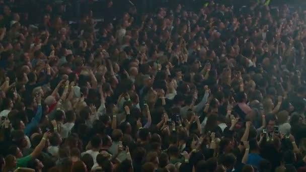 dav diváků a fanoušků na rockovém koncertě tančí a natáčí hudebníky na chytrých telefonech