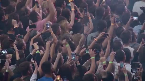 a crowd of spectators and fans at a rock concert dancing and filming musicians on smartphones
