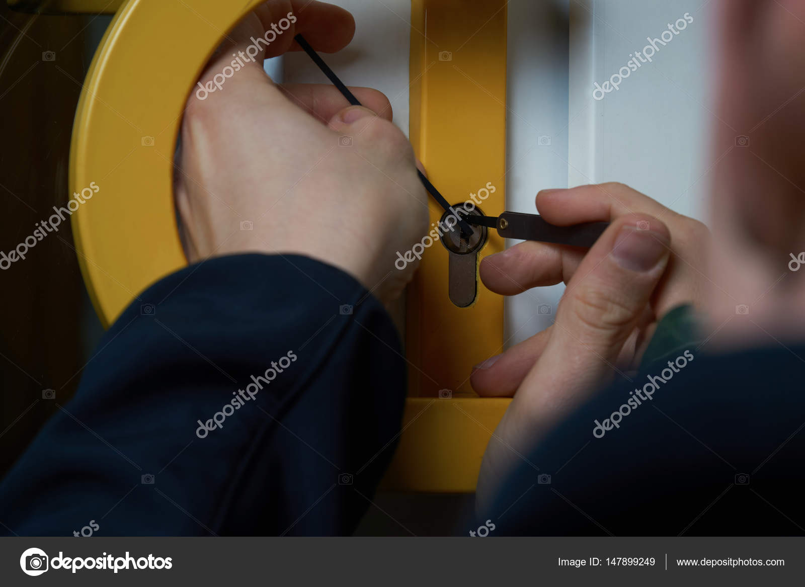 Burglar with lockpick tool opens the front door to enter the house ...