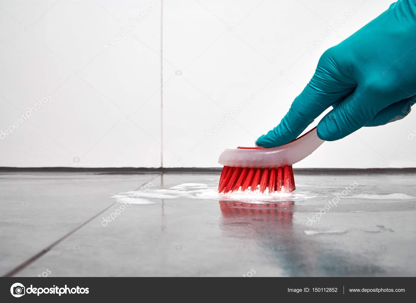 Maschio a mano con pennello rosso pulizia piastrelle del bagno al