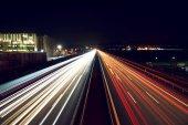 Fotografie Lichtspuren auf der Autobahn mit einem Industriegebäude - leicht getönt