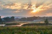 Fotografie Sonnenaufgang über eine malerische Landschaft mit Seen, Hügeln und Nebel. Lebendige Farben mit dramatische Wolken. Wilhelminenaue, Bayreuth, Deutschland