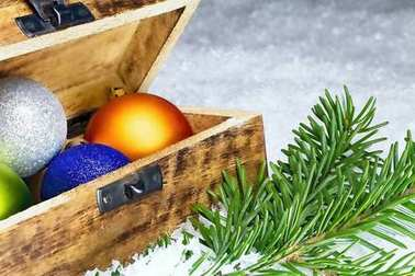 Christmas decorations with Christmas balls in a chest and spruce branch. Merry Christmas.