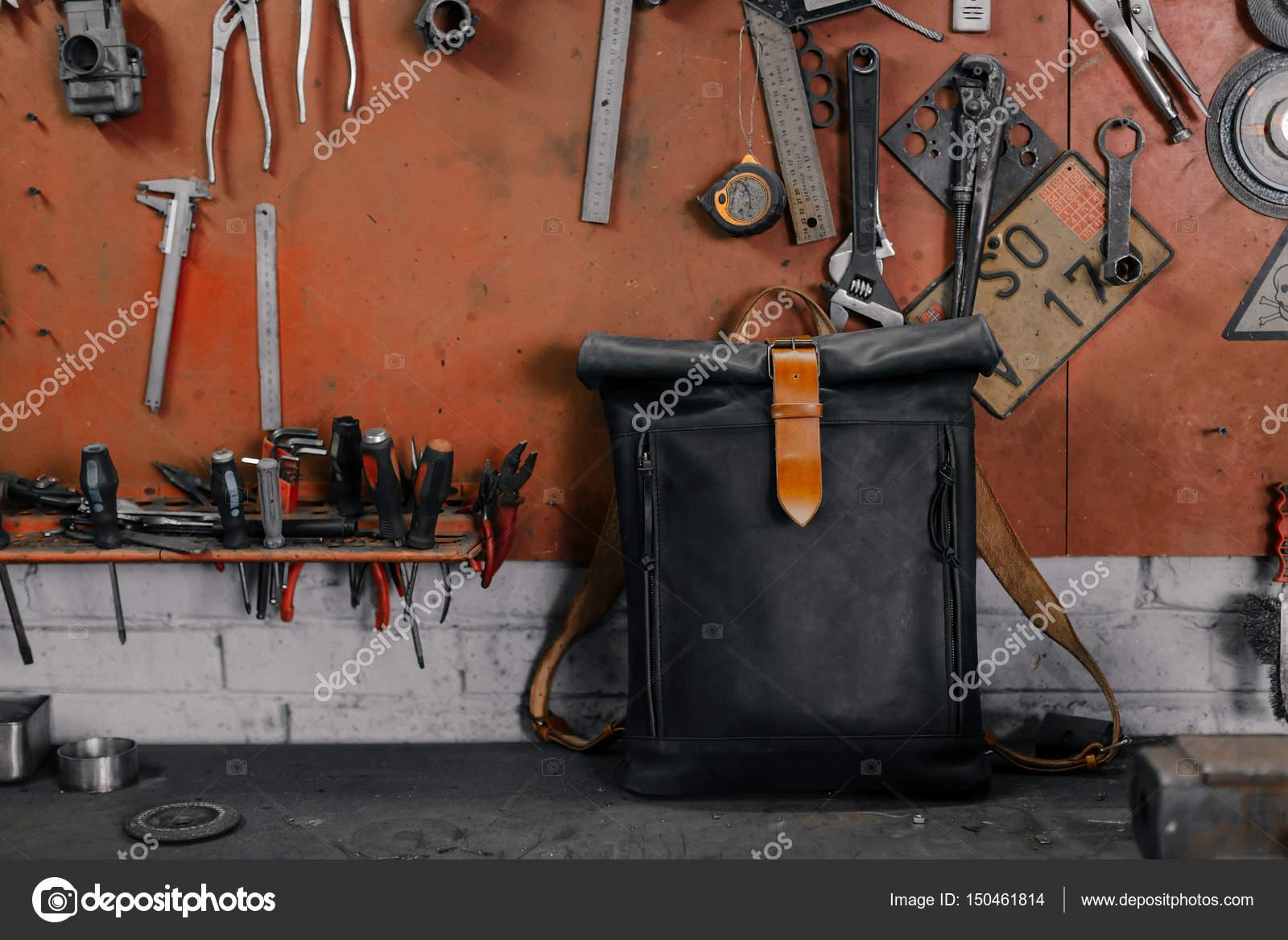 Exkluzivní černý kožený batoh. Batoh u zdi. Nástroje v garáži. Mnoho  různých nástrojů 066da058ae