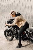 Photo Woman sitting on her motorcycle. Motorcycle near a grey wall. girl looks at herself in the mirror of the motorcycle. girl with short hair. girl in black glasses and a leather jacket. Bike