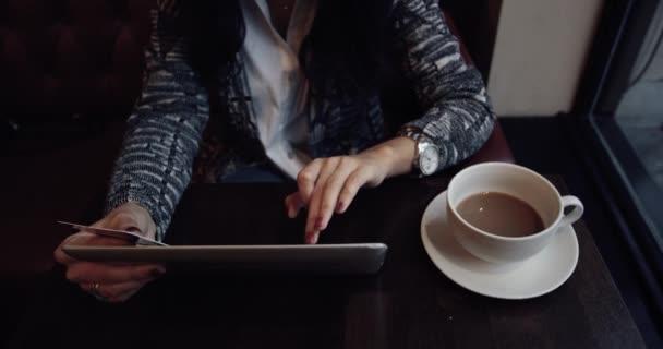 Mladá žena dělá online nakupování na tabletu v kavárně. 4k