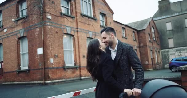 Young attractive tourist couple embracing and kissing in a romantic destination city, enjoying each other company and being close on a summer holiday trip. Travel and lifestyle outdoors. 4k