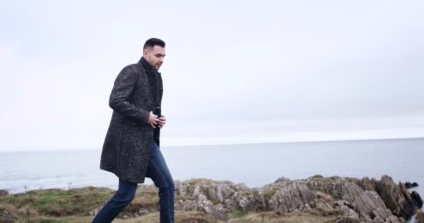 Man walks into frame and stands, looking out over vast ocean and cloudy sky in Ireland, model released. 4k. slow motion
