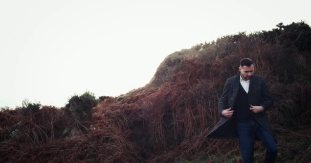 Man walks into frame and stands, looking out over vast ocean and cloudy sky in Ireland, model released. 4k