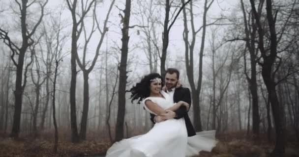 Šťastný svatební pár, ženich, otáčí svou nevěstu v lesích, zpomalené. 4k