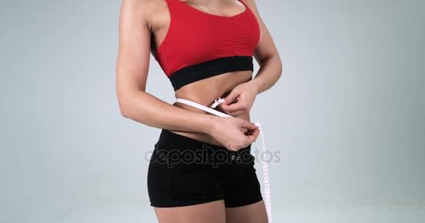 Sportovní ženské tělo, kde ona je měření s páskou na břiše na bílém pozadí. 4k