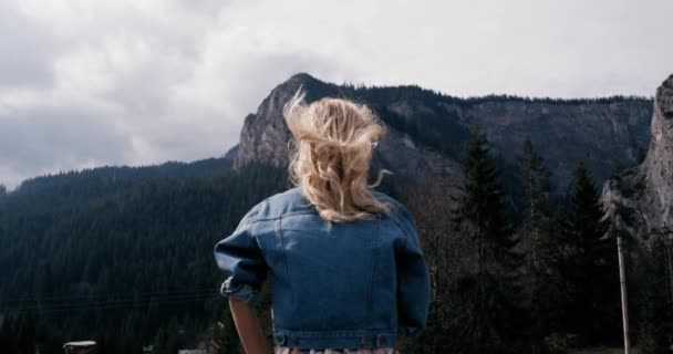 Success concept -Rural landscape. Fit woman with arms raised victoriously celebrating successful evening hike at beautiful sunset. Female model standing on top of the seaside mountain in worship pose
